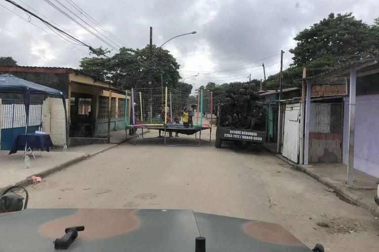 Brinquedo pula-pula no meio da rua, em favela da zona oeste do Rio, enquanto um tanque com soldados tenta passar